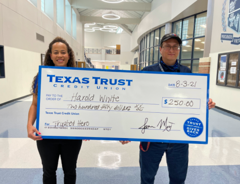 """Harold White receives a $250 check as a winner of the Texas Trust Credit Union """"Trusted Heroes"""" Award. White earned the award in recognition of his efforts as the nighttime custodial staff lead. """"They called me in one day to come in early and said that I was being recognized for something. That's about all I knew,"""" he said."""